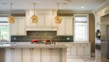 Elegant pearl glazed cabinets with green backsplash.